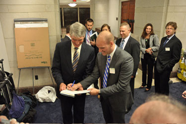 Josh Seefried, an officer in the Air Force and co-founder of OutServe, signs a copy of his book, Our Time, for Sen. Mark Udall (D-Colo.).