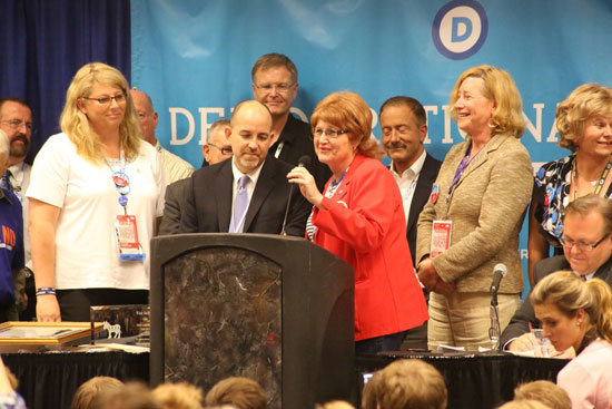 DNC director of constituency outreach, Brian Bond, left at lectern, stands with transgender DNC committee member Babs Siperstein. Dr. Dana Beyer is immediately right of Siperstein