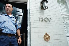 A police officer guards the entrance to the Swann Street townhouse where Robert Wone was murdered.