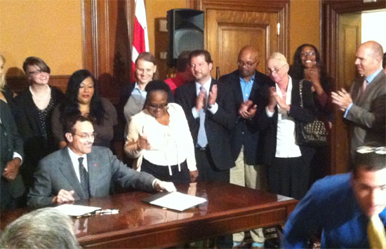 Surrounded by activists, Mayor Vincent Gray signed two pro-LGBT bills, the JaParker Deoni Jones Birth Certificate Equality Amendment Act and the Marriage Officiant Act, into law Tuesday afternoon. Photo by John Riley