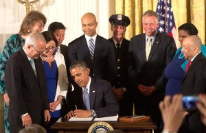 Photo: Barack Obama signs an LGBT nondiscrimination executive order. Credit: Pete Souza/White House.