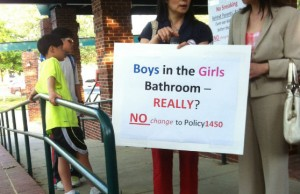 A parent holds up a sign opposing Policy 1450, which adds gender identity to Fairfax County Public Schools' nondiscrimination policy.