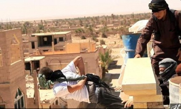 ISIS fighters push a man from a building, File Photo