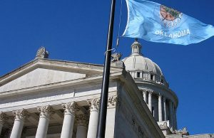 The Oklahoma Flag waving outside of the Oklahoma State Capitol (Photo: Okiefromokla, via Wikimedia).