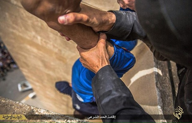 ISIS militants hold a man over the edge of a building