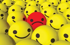 Unhappy face in sea of smilies