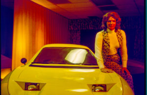 Elizabeth Carmichael sitting on yellow car